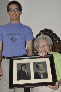 Harriet Sitting in her Grandfather's Photo Chair holding her Grandparents photos. That's my son smiling next to her. Sept. 10, 2010